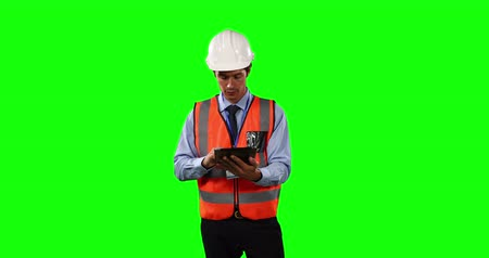 firma : Front view of a Caucasian man wearing a helmet and high visibility vest, using his tablet on green screen background.