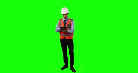 firma : Front view of a Caucasian man wearing a helmet and high visibility vest, counting and using his tablet on green screen background.