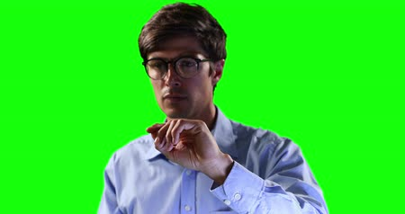 firma : Front close up view of a Caucasian man wearing a shirt and glasses, with arms raised and hands out in front of him, with his fingers moving in front of camera, touching a virtual interactive screen on green screen background.