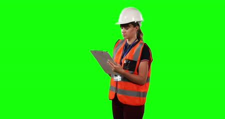 firma : Front view of a Caucasian woman wearing a helmet and high visibility vest, counting and writing down a number in a folder on green screen background. Wideo