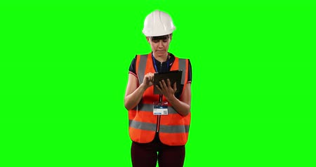 firma : Front view of a Caucasian woman wearing a helmet and high visibility vest, counting and using a tablet on green screen background. Wideo