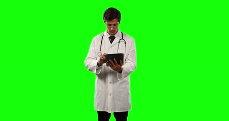 muž : Front view of a Caucasian male doctor wearing a lab coat and stethoscope, using a tablet on green screen background.