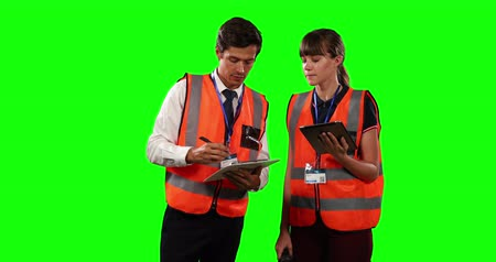 firma : Front view of a Caucasian man and woman wearing high visibility vests, discussing and comparing data, using a folder and a tablet on green screen background. Wideo