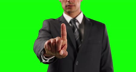 muž : Front view mid section of a Caucasian businessman wearing smart clothes, with arm raised and hand out in front of him, with his index finger facing camera, touching a virtual interactive screen on green screen background.
