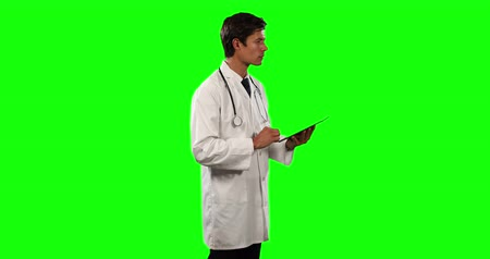 muž : Side view of a Caucasian male doctor wearing a lab coat and stethoscope, using a tablet on green screen background. Dostupné videozáznamy