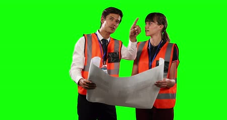 muž : Front view of a Caucasian man and woman wearing high visibility vests, discussing plans and holding together architectural drawing on green screen background.
