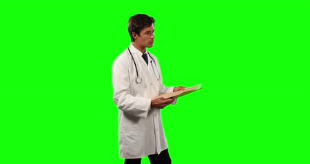 muž : Side view of a Caucasian male doctor wearing a lab coat and stethoscope, holding a folder on green screen background.