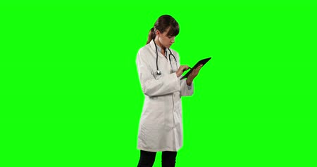 ocupações : Side view of a Caucasian female doctor wearing a lab coat and stethoscope, using a tablet on green screen background.