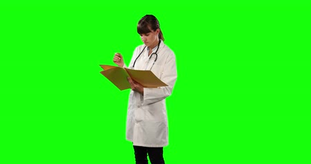 ocupações : Front view of a Caucasian female doctor wearing a lab coat and stethoscope, holding a folder and reading notes on green screen background. Vídeos