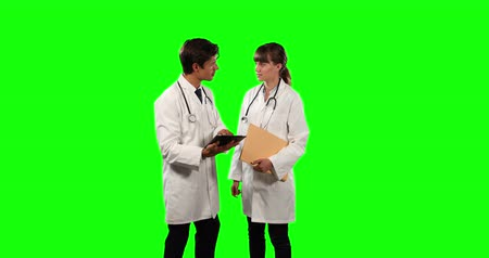 muž : Front view of two Caucasian male and female doctors wearing lab coats and stethoscopes, discussing and using a tablet, holding a folder, on a green screen background. Dostupné videozáznamy