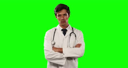 muž : Portrait of a Caucasian male doctor wearing a lab coat and stethoscope, standing with his arms crossed and looking straight into a camera on green screen background. Dostupné videozáznamy