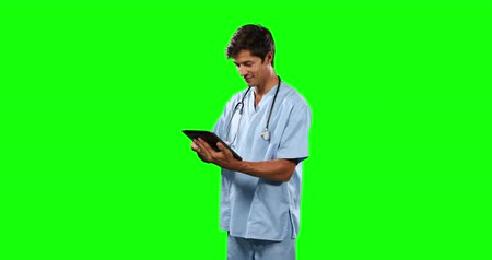 一人 : Front view of a Caucasian male doctor wearing blue scrubs and stethoscope, using a digital tablet on green screen background.