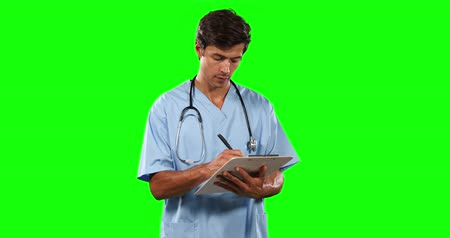 muž : Portrait of a Caucasian male doctor wearing blue scrubs and stethoscope, writing in a folder, smiling looking straight into a camera on green screen background.