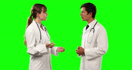 muž : Side view close up of two Caucasian male and female doctors wearing lab coats and stethoscopes, standing and talking, on green screen background.