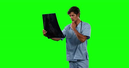 muž : Side view of a Caucasian male doctor wearing blue scrubs and stethoscope, watching an x-ray picture, on green screen background. Dostupné videozáznamy