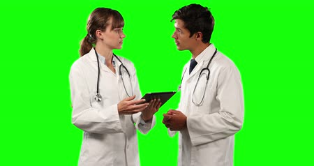 muž : Front view close up of two Caucasian male and female doctors wearing lab coats and stethoscopes, discussing and using a tablet, on a green screen background.