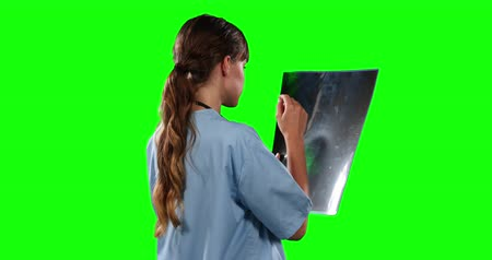 ocupações : Rear view close up of a Caucasian female doctor wearing blue scrubs and stethoscope, watching an x-ray picture, on green screen background.