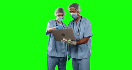 muž : Front view of two Caucasian female and male doctors wearing blue scrubs and face masks, discussing and using a laptop computer on green screen background.