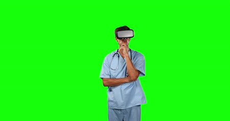 一人 : Front view of a Caucasian male doctor wearing blue scrubs and Virtual Reality glasses, standing with his arms crossed on green screen background.