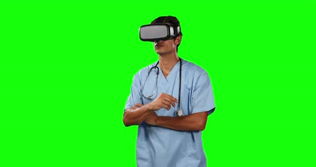 очки : Front view of a Caucasian male doctor wearing blue scrubs and Virtual Reality glasses, and pointing to a virtual screen on green screen background. Стоковые видеозаписи