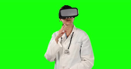 ocupações : Front view close up of a Caucasian female doctor wearing a lab coat and Virtual Reality glasses, and pointing to a virtual screen on green screen background. Vídeos