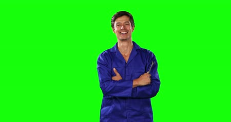 prendas de vestir : Portrait of a happy Caucasian male engineer car mechanic with short dark hair standing with his arms crossed, holding a wrench, smiling and looking straight into a camera on green screen background.