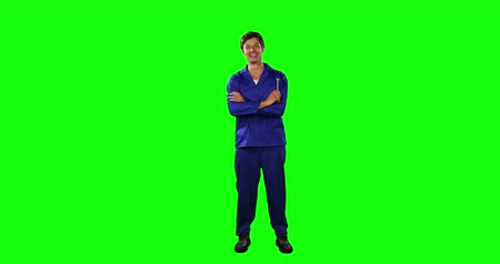 mutlu : Portrait of a happy Caucasian male engineer car mechanic with short dark hair standing with his arms crossed, holding a wrench, smiling and looking straight into a camera on green screen background.