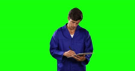 firma : Side view of a happy Caucasian male engineer car mechanic with short dark hair standing and writing in a folder, wearing work clothes and smiling on green screen background