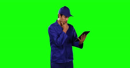 一人 : Side view of a happy Caucasian male engineer car mechanic with short dark hair standing holding a digital tablet, wearing work clothes and cap on green screen background