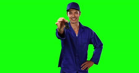 mutlu : Portrait of a happy Caucasian male engineer car mechanic wearing wearing work clothes and cap, holding car keys, smiling and looking straight into a camera on green screen background.