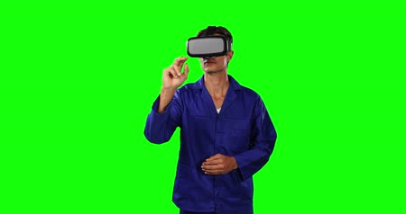 prendas de vestir : Front view of a Caucasian male engineer car mechanic wearing wearing work clothes and a Virtual Reality headset, pointing to a virtual screen on green screen background. Archivo de Video