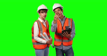 muž : Front view of a Caucasian man and woman wearing high visibility vests and helmets, discussing plans, using a tablet and holding architectural drawings on green screen background. Dostupné videozáznamy