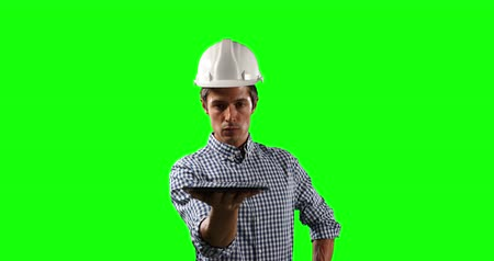 firma : Front view of a Caucasian male architect engineer wearing a white helmet and shirt, holding a digital tablet in front of him on green screen background.