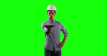 muž : Front view of a Caucasian male architect engineer wearing a white helmet and shirt, holding a digital tablet in front of him on green screen background.
