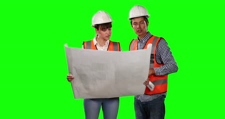 muž : Front view of a Caucasian man and woman wearing high visibility vests and helmets, discussing plans and holding together architectural drawing on green screen background. Dostupné videozáznamy