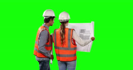 firma : Rear view of a Caucasian man and woman wearing high visibility vests and helmets, discussing plans and holding architectural drawings on green screen background.