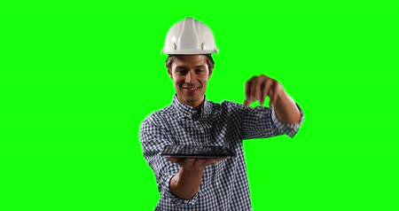 prendas de vestir : Front view of a Caucasian male architect engineer wearing a white helmet and shirt, holding a digital tablet in front of him on green screen background.