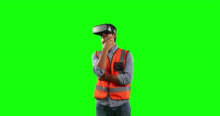 firma : Front view of a Caucasian man wearing high visibility vest and and Virtual Reality glasses, smiling and standing on green screen background.