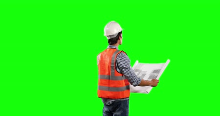 muž : Rear view of a Caucasian man wearing high visibility vest and helmet, holding architectural drawing on green screen background.