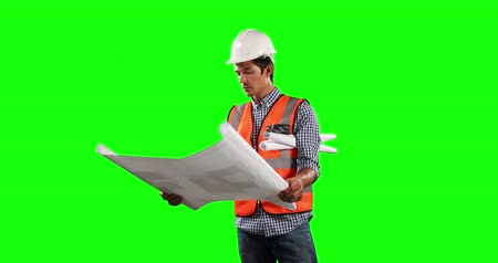 muž : Front view of a Caucasian man wearing high visibility vests and helmet, holding architectural drawing and smiling on green screen background.
