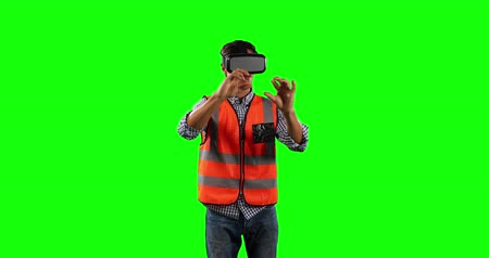 szervez : Front view of a Caucasian man wearing high visibility vest and and Virtual Reality glasses, touching a virtual interactive screen on green screen background.