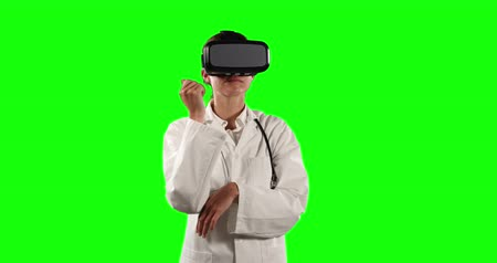 очки : Front view close up of a Caucasian female doctor wearing a lab coat and Virtual Reality glasses, pointing to a virtual screen on green screen background. Стоковые видеозаписи