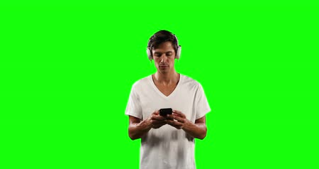 t şeklinde : Front of a Caucasian man with short dark hair, wearing a white t-shirt and headphones, smiling listening to musing and using his smartphone on green screen background. Stok Video