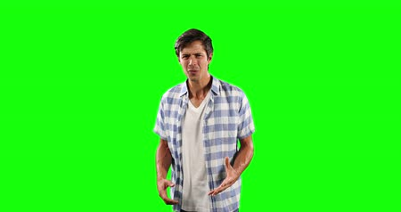 prendas de vestir : Portrait of a disgusted Caucasian man with short dark hair, wearing a  checkered shirt, looking straight into a camera on green screen background. Archivo de Video