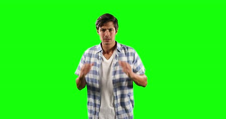 一人 : Portrait of a worried Caucasian man with short dark hair, wearing a  checkered shirt, looking straight into a camera on green screen background. 動画素材