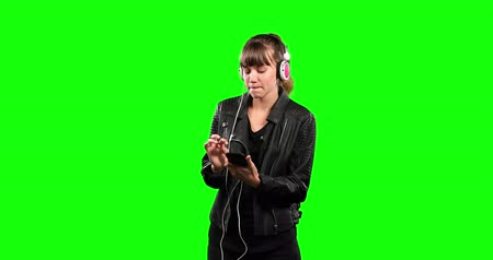 felnőtt : Front of a Caucasian woman with long dark hair, wearing black leather jacket and headphones, smiling listening to musing and using his smartphone on green screen background.
