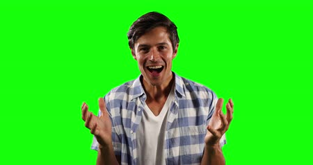 一人 : Portrait of a happy Caucasian man with short dark hair, wearing a checkered shirt, looking straight into a camera on green screen background. 動画素材
