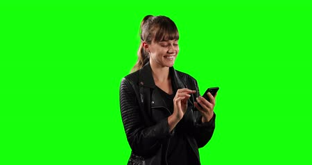 felnőtt : Front view close up of a happy Caucasian woman with long dark hair,a leather jacket, smiling and using her smartphone on green screen background.