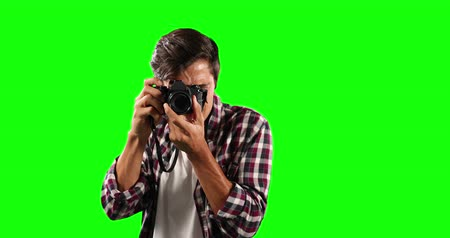 一人 : Portrait of a Caucasian man with short dark hair, wearing a  checkered shirt, holding a camera and taking pictures, looking straight into a camera on green screen background. 動画素材