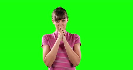felnőtt : Portrait of a incomprehensible Caucasian woman with long dark hair, wearing a stripped t-shirt, moving her hands, looking straight into a camera on green screen background. Stock mozgókép